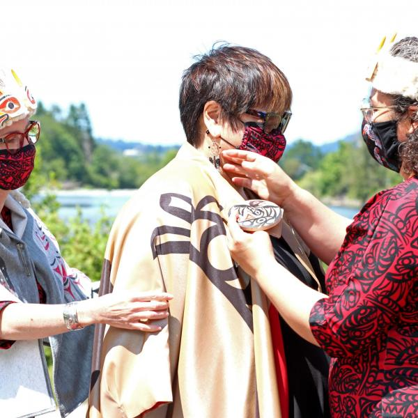 Dr. Judith Sayers is robed by Ay Lelum co-owners, Aunalee and Sophia