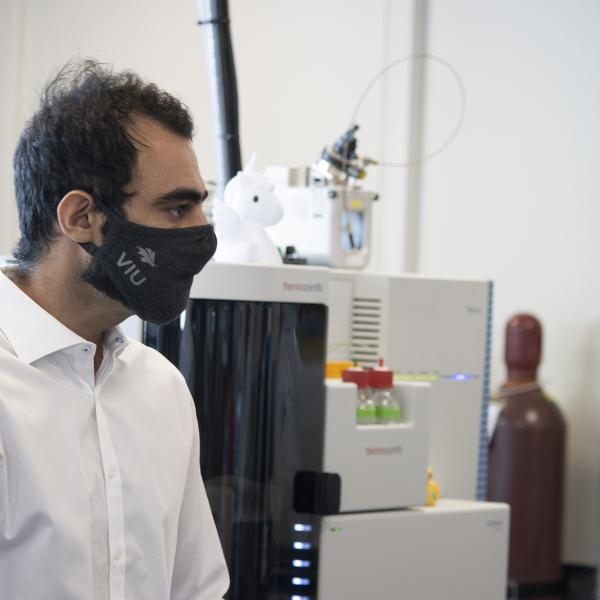Armin Saatchi stands in front of the Thermo Fisher Scientific Orbitrap Mass Spectrometer System