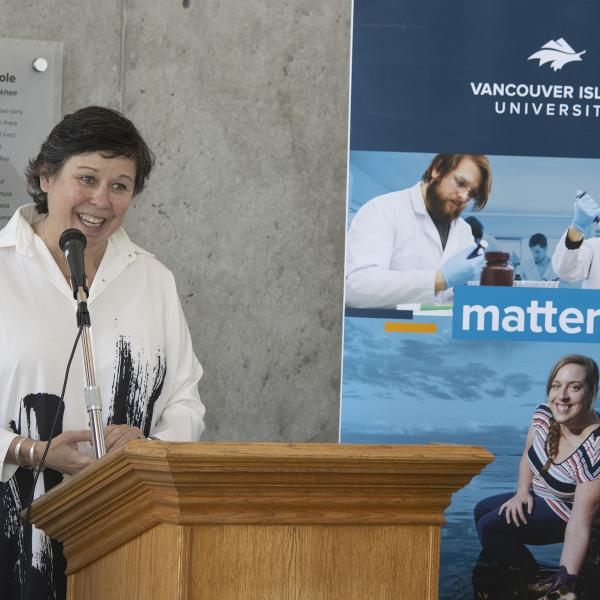Dr. Deborah Saucier, VIU President and Vice-Chancellor, stands in front of a podium smiling.