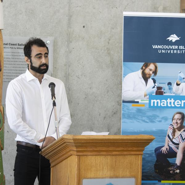 Armin Saatchi, a VIU graduate student, stands at a podium during the BC government funding announcement.