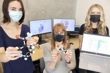 Students and a professor at VIU hold models of molecules in their hands.