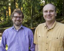 Dr. Erik Krogn and Dr. Chris Gill stand beside each other in a wooded area