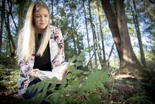 Mandy Hobkirk uses an identification book while examining plants at VIU's Nanaimo Campus.