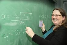 Lisa Lewis, VIUs acting chair of Adult Basic Education, draws math equations on a chalkboard while holding a cellphone