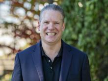 Photo of Dr. Richard Lane, smiling with greenery behind him
