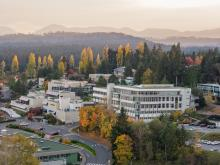 An aerial view of VIU's Nanaimo campus during the fall trees dappled with yellow and orange leaves.