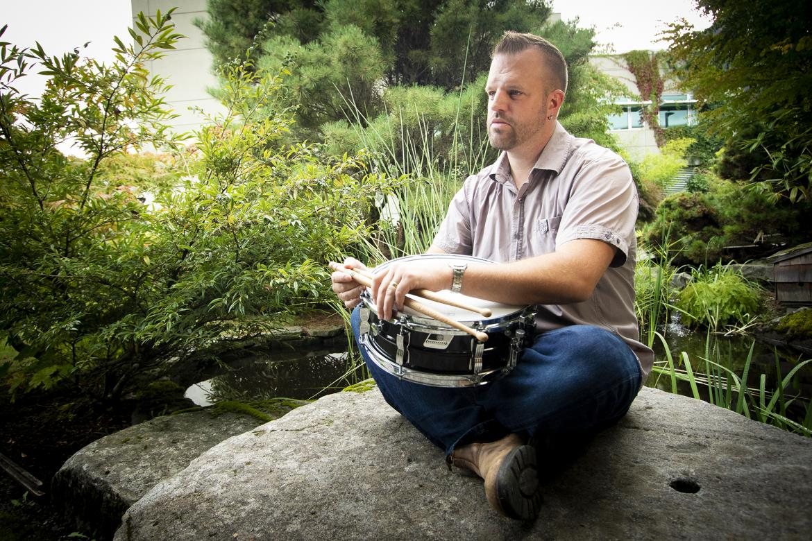 VIU Music Department Instructor Hans Verhoeven sits on a rock near a pond holding a drum.