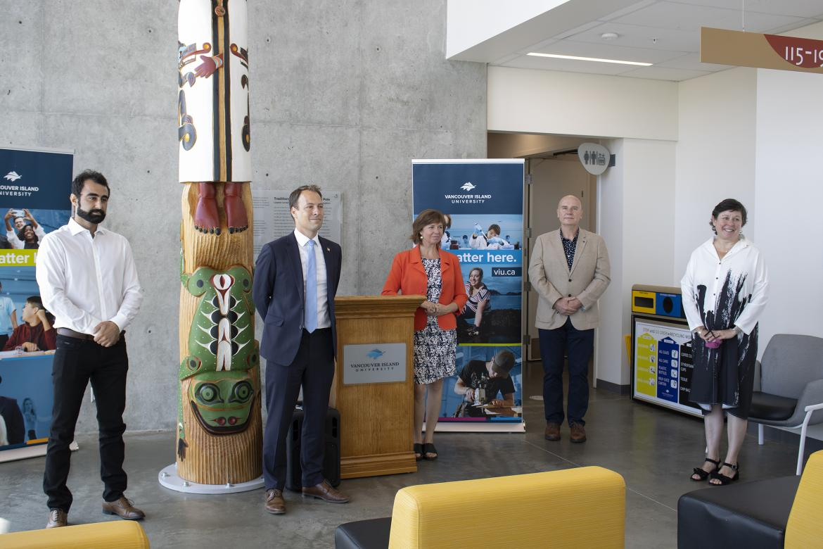 Five people stand in VIU's Health and Science Centre during a media conference.
