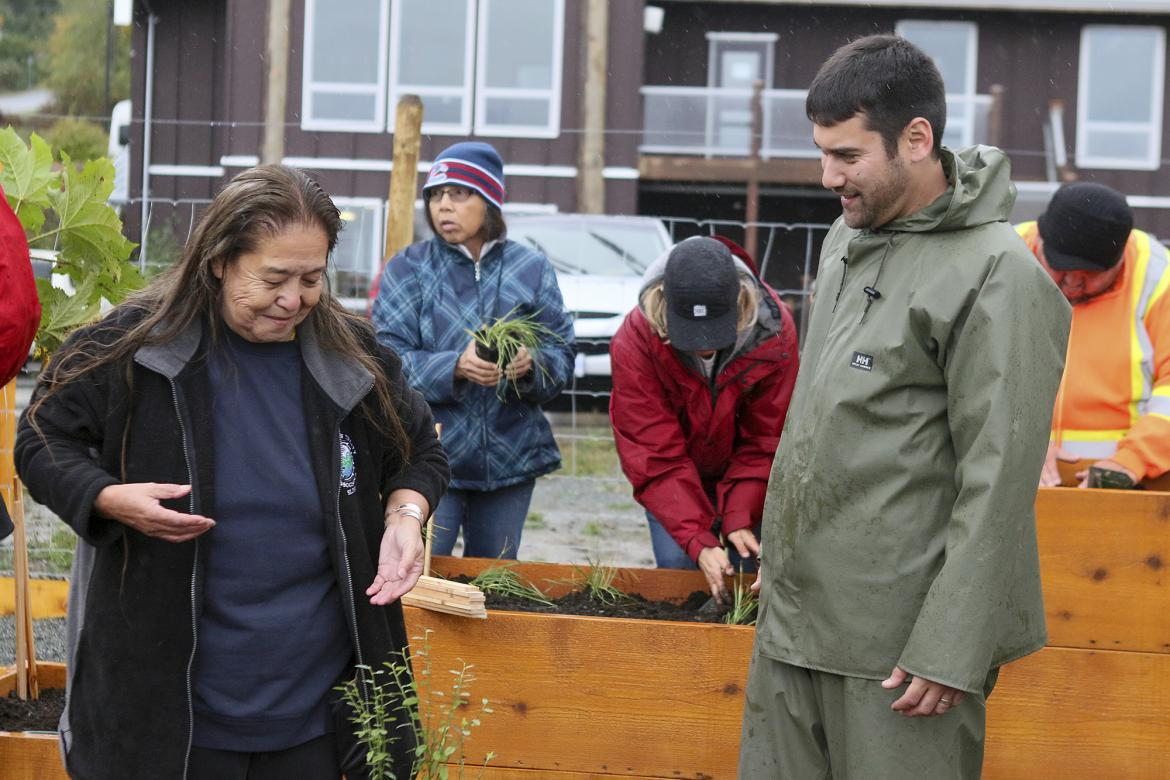 Elder Bonnie Jones and Graham Sakaki, MABRRI Research and Community Engagement Coordinator, plant seedlings in the Garden of Spiritual Healing at the Snaw-Naw-As Health Centre.