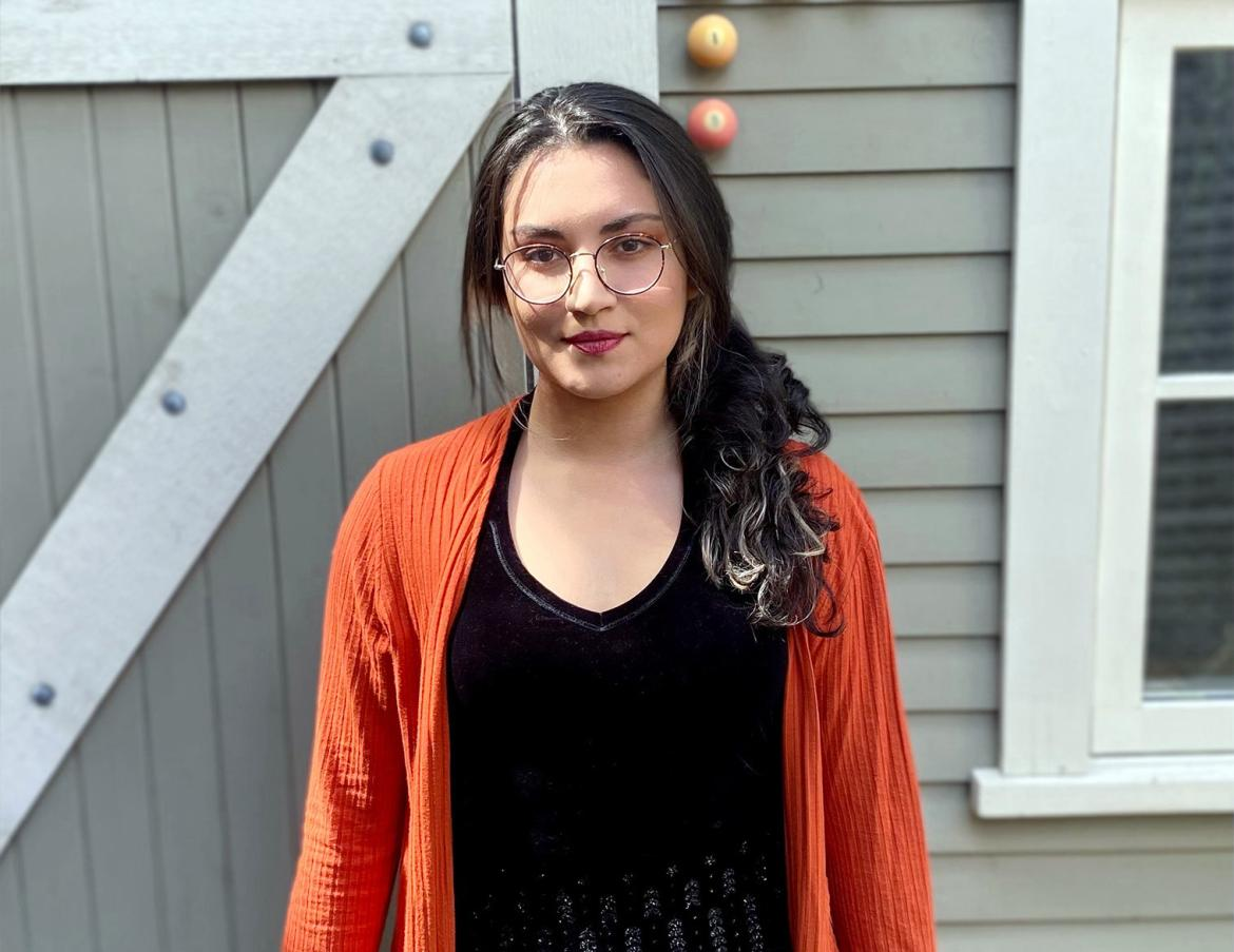 Sara Guzman stands in front of a building, wearing an orange sweater.