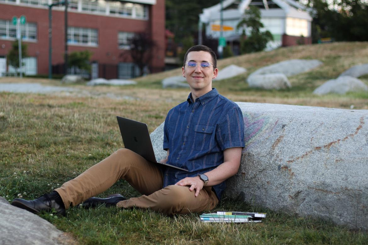 Spenser Smith, a VIU Creative Writing alum, seated outdoors with his laptop