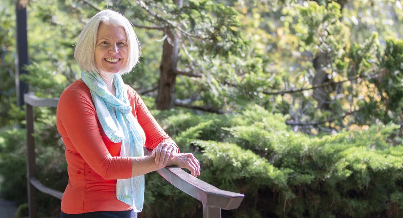 Dr. Cynthia-Lou Coleman leans against a railing near VIU's koi pond with sun hitting her hair.