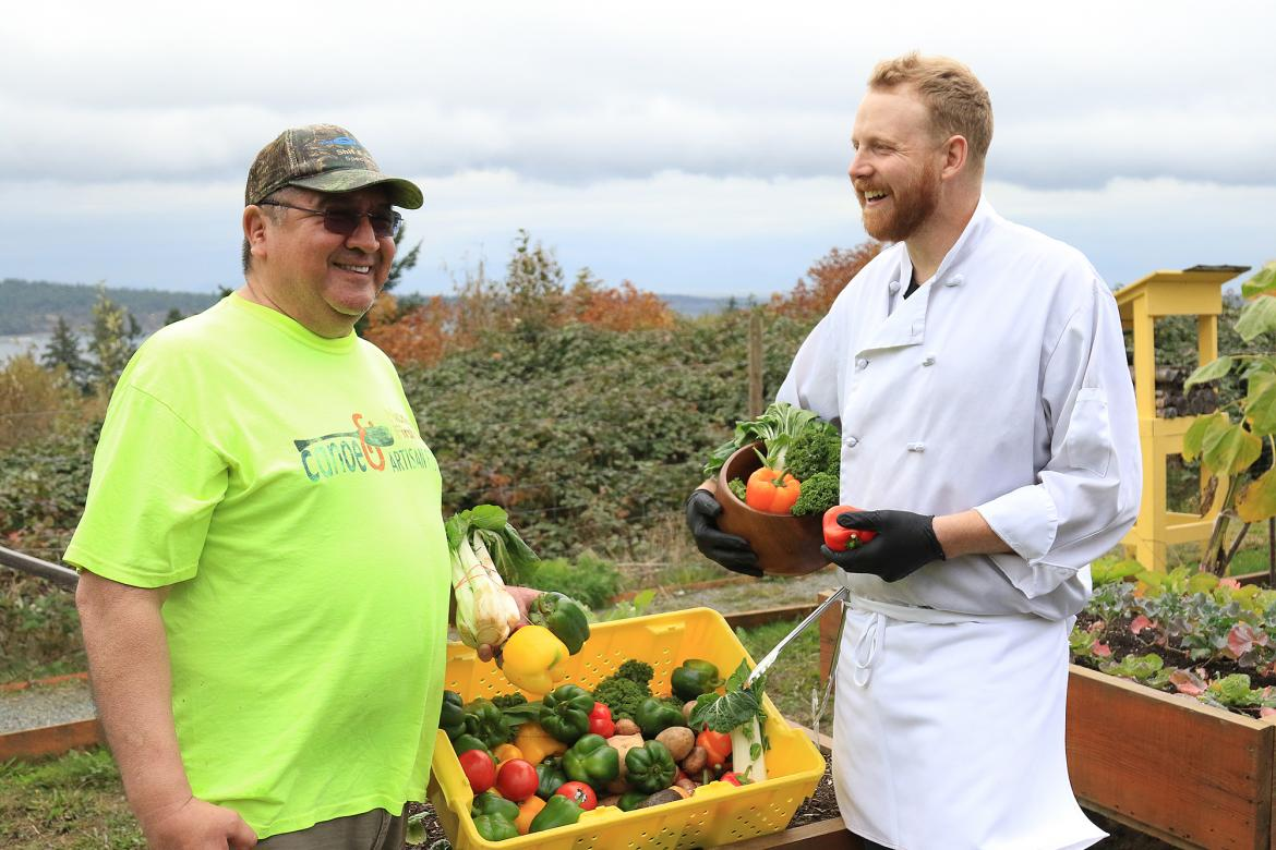James Cook, left, a volunteer for the Loaves and Fishes Food Bank and Sean Weins, Garden Café Chef, share stories in the Snaw-Naw-As Health Centre's Garden of Spiritual Healing.