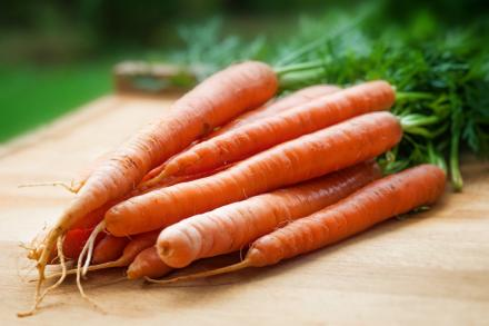 A bundle of carrots on a cutting board