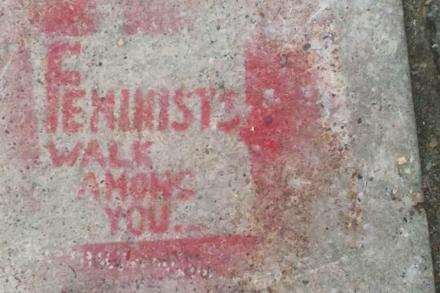 "A light grey concrete sidewalk is spray painted with the phrase ""Feminists Walk Among You."""