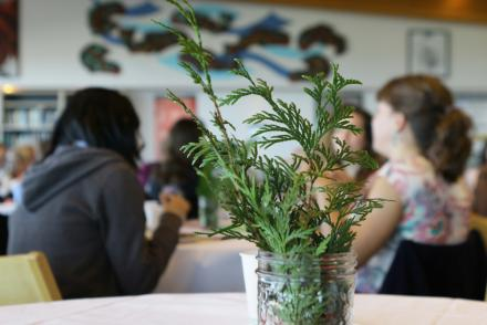 Cedar branch in a jar in foreground, people in VIU's Gathering Place in background