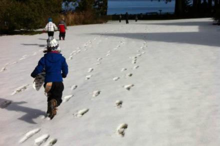 Children running across a snowy lawn