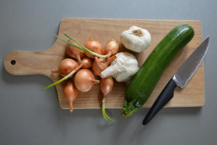 A cutting board with onions, garlic and zucchini